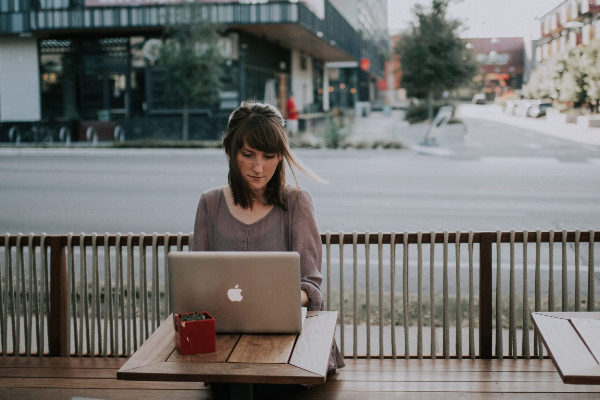 Woman with brown hair writing blogging tips article on laptop sitting outside at restaurant