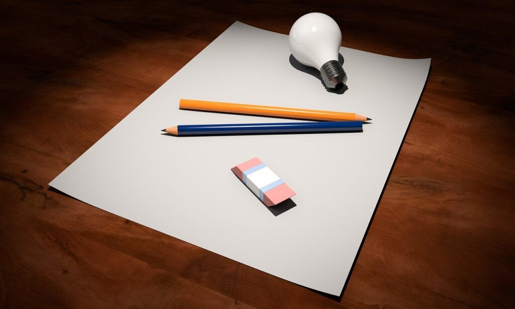 On top of a white piece of paper, there is a lightbulb, an orange colored pencil, a blue colored pencil, and an eraser.